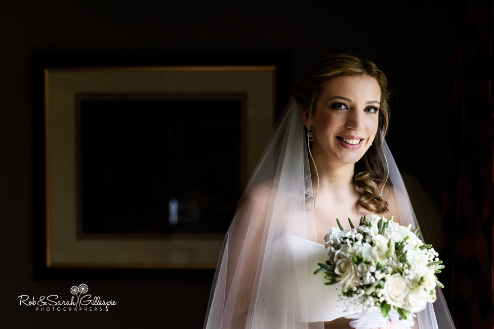 Portrait of bride in window light, with long veil