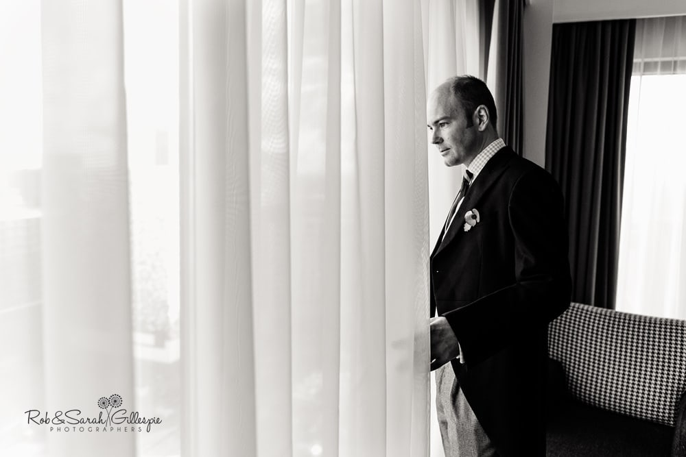 Groomsman looks through window at Hyatt Hotel in Birmingham