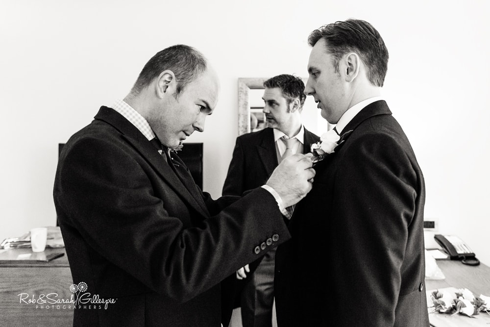 Groomsmen help groom get ready for wedding