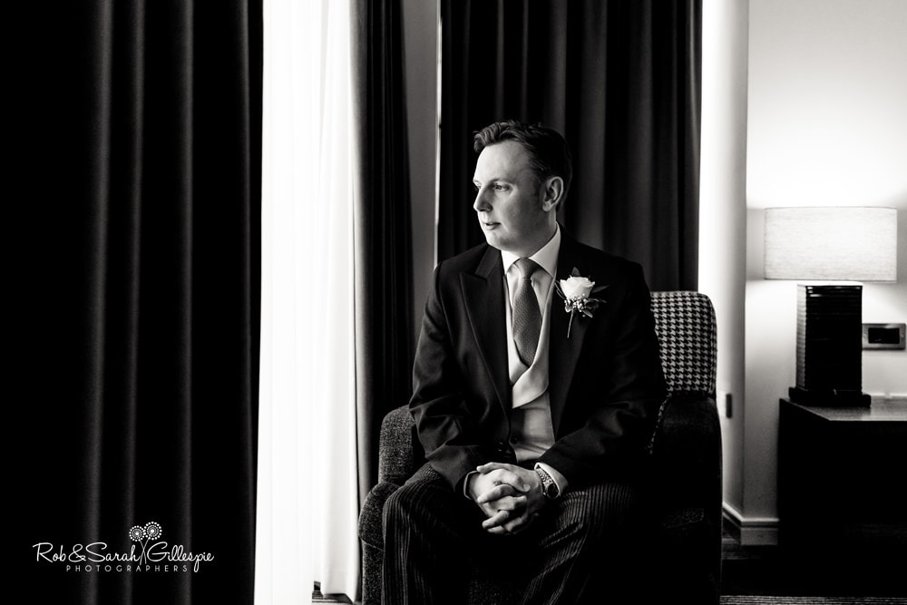Groom seated in window light at Hyatt Hotel Birmingham