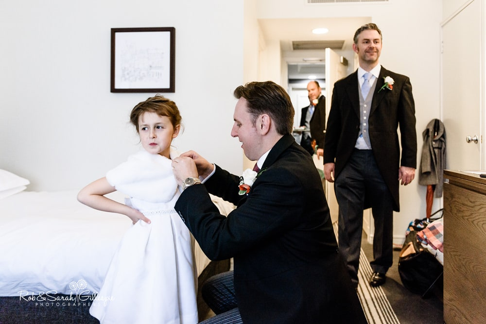 Flowergirl has outfit fastened by father while getting ready for wedding