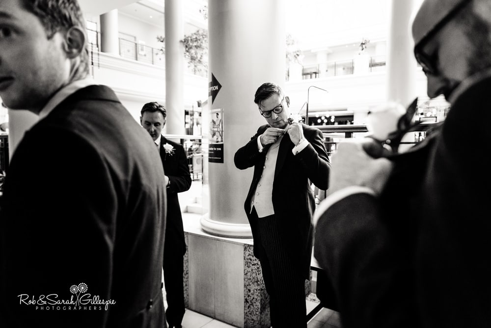 Groomsmen fix buttonhole flowers at Hyatt Hotel Birmingham