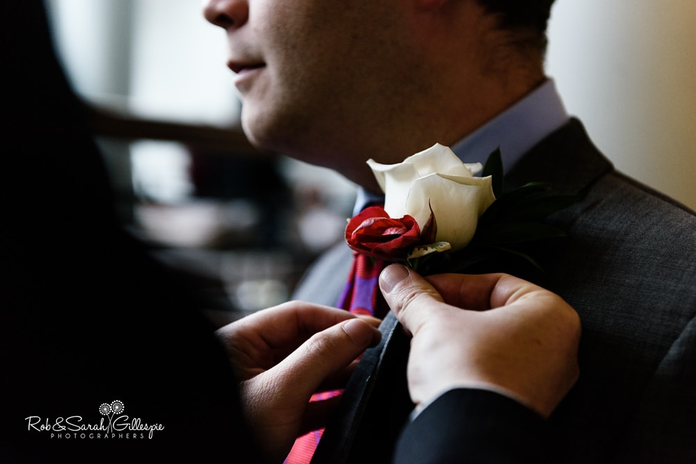 Groomsmen fix buttonhole flowers