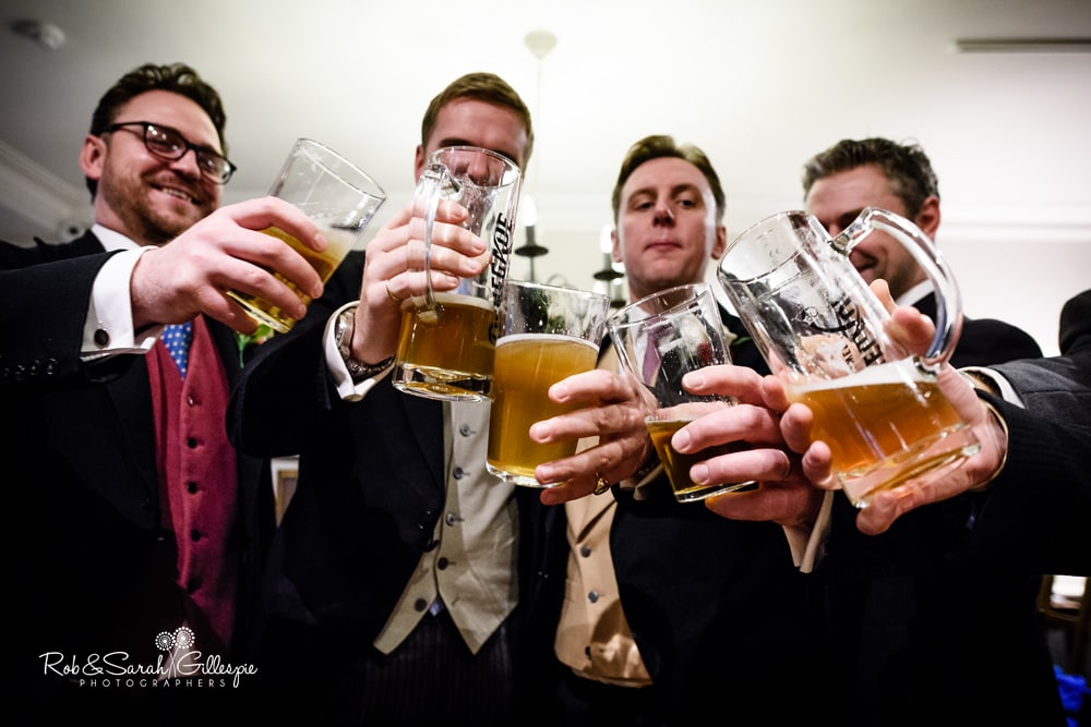 Groom and groomsmen enjoy drink before wedding