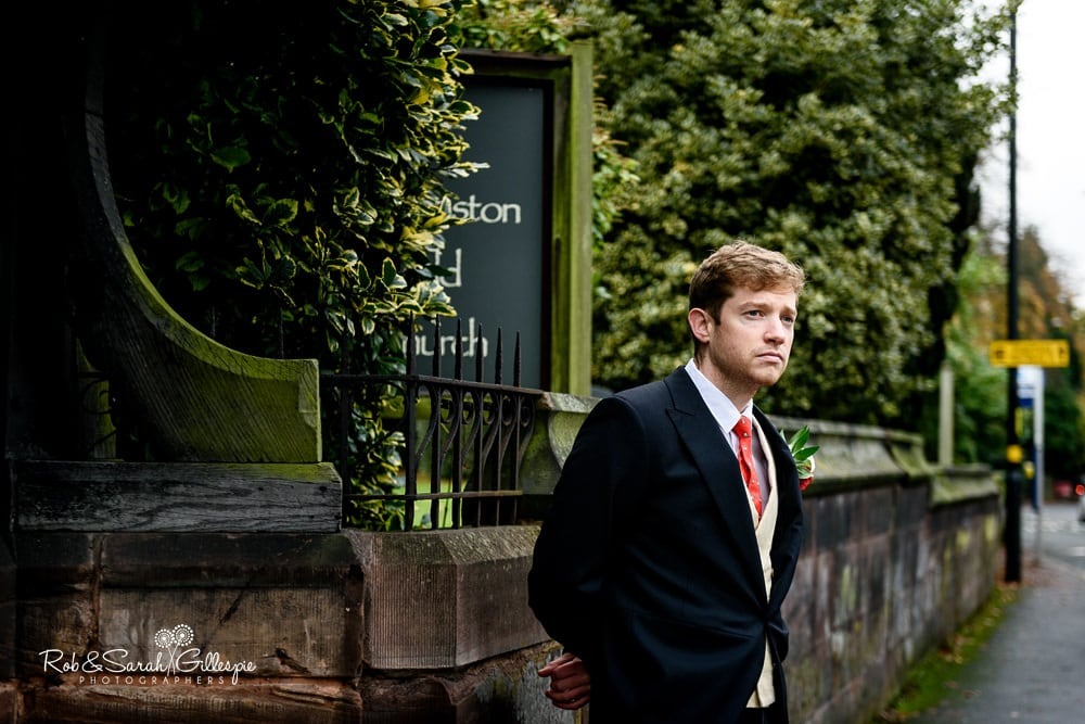 Groomsman waits for bride to arrive at Edgbaston Old Church in Birmingham