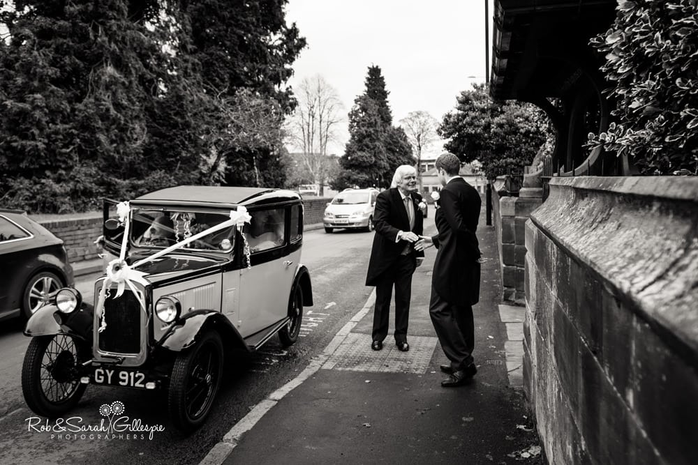 Bride's father and groomsman shake hands as bride's car arrives