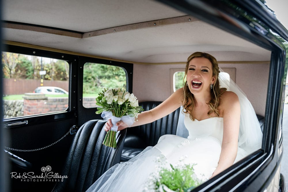 Bride laughing in her wedding car as she arrives at church for wedding