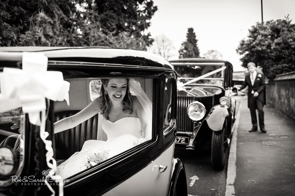 Bride smiling as she gets out of wedding car