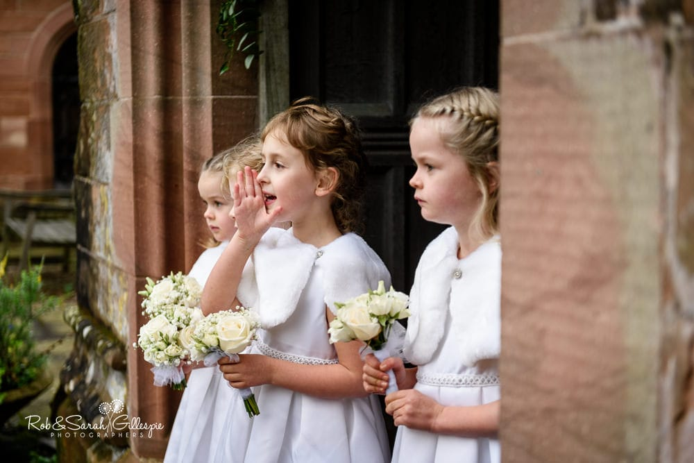 Flowergirls wait for bride at church entrance