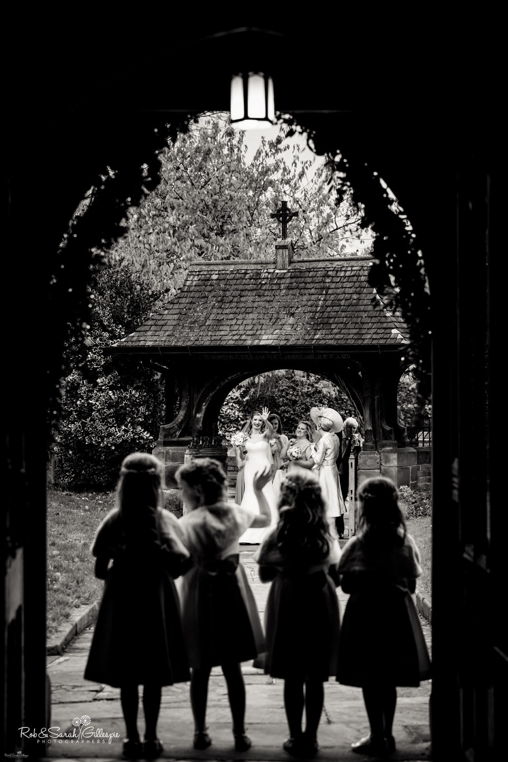 Bride waves to flowergirls as she arrives at wedding