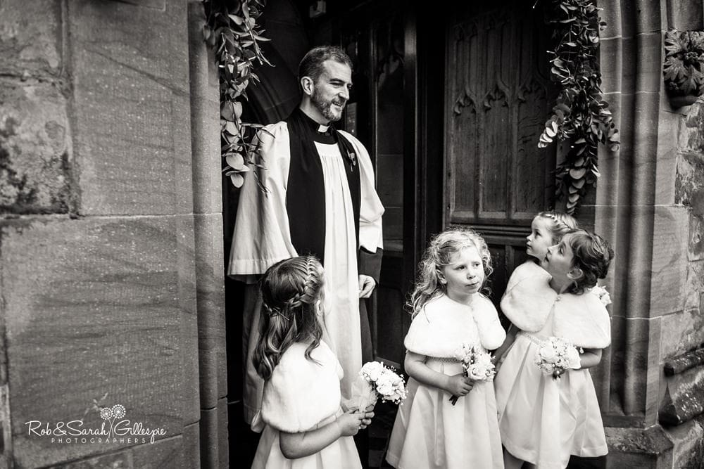Flowergirls and vicar wait for bride