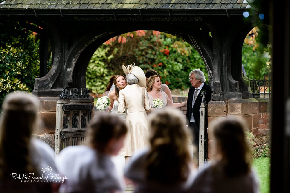 Bride kisses her mum while flowergirls look on