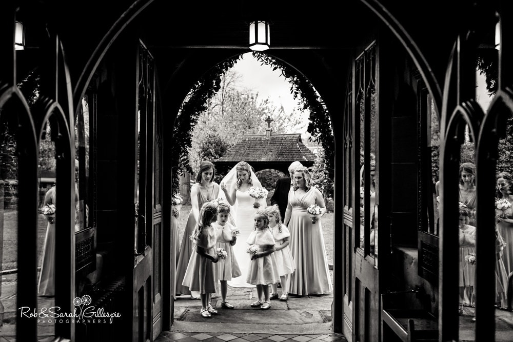 Bride, bridesmaids and flowergirls final moments outside church entrannce before wedding service begins