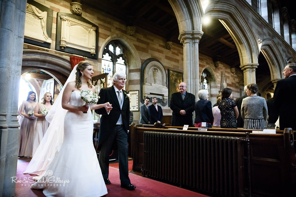 Bride and father enter Edgbaston Old Church for wedding service, followed by bridesmaids