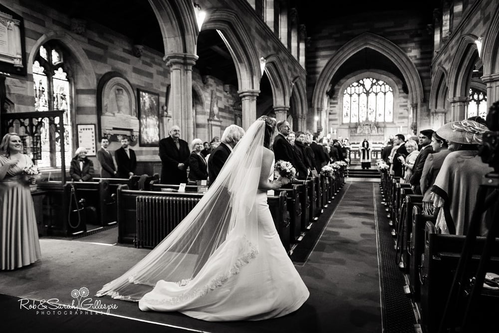 Bride enters Edgbaston Old Church , with veil behind her and vicar looking on