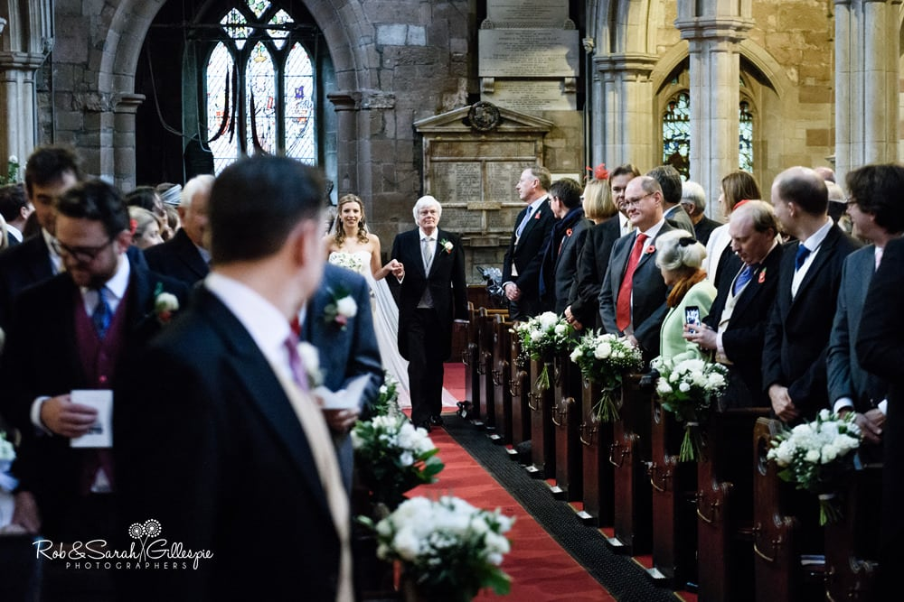 Bride and father walk up aisle as groom turns around to see her