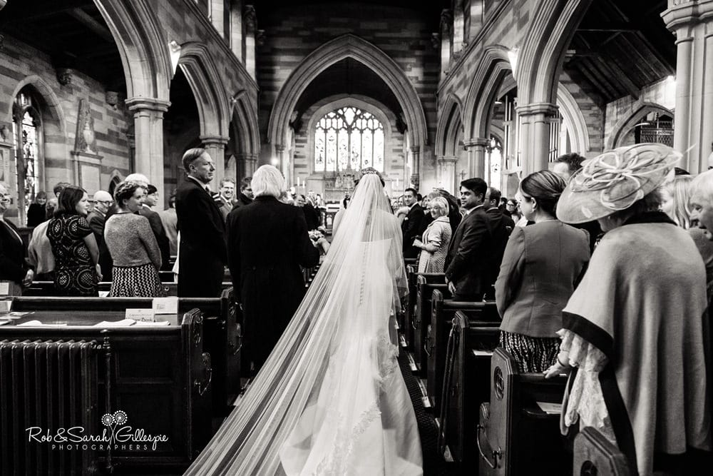 Bride and father walk up aisle as veil spreads out behind her