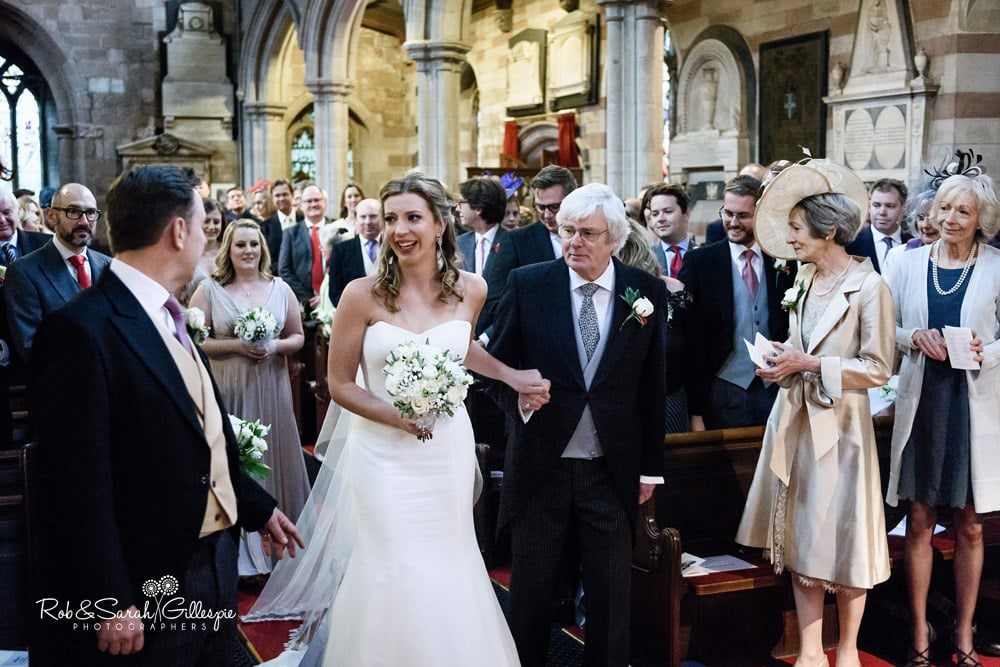 Bride and groom smile at each other during wedding ceremony at Edgbaton Old Church