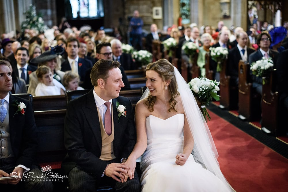Bride and groom hold hands and smile at each other during wedding service