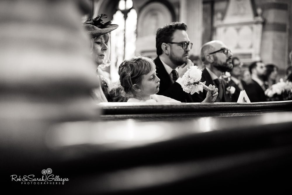 Flowergirl inspecting her flowers while other guests listen to vicar
