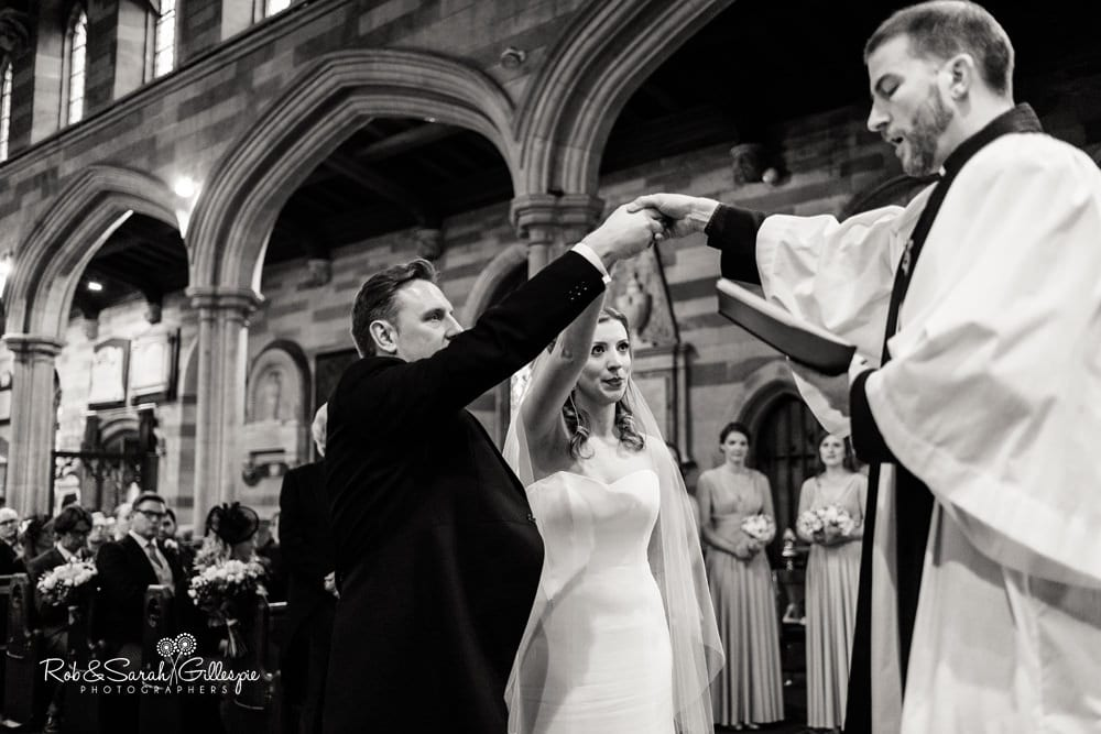 Bride and groom receive blessing from vicar during wedding service