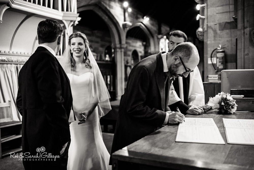 Bride and groom smile at each other as their witnesses sign marriage register