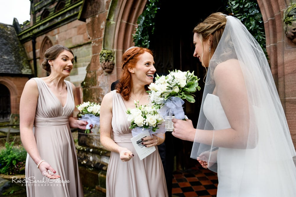 Two bridesmaids smiling at bride after wedding service