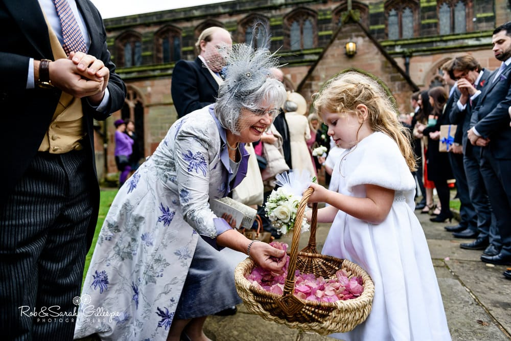 Flowergirl hands out confetti to wedding guests