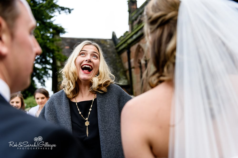 Wedding guest laughing as she congratulates bride and groom