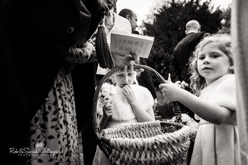 Flowergirls hand out confetti to wedding guests