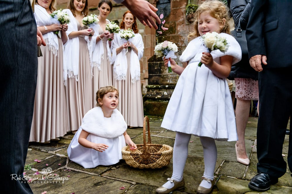 Flowergirls play with confetti