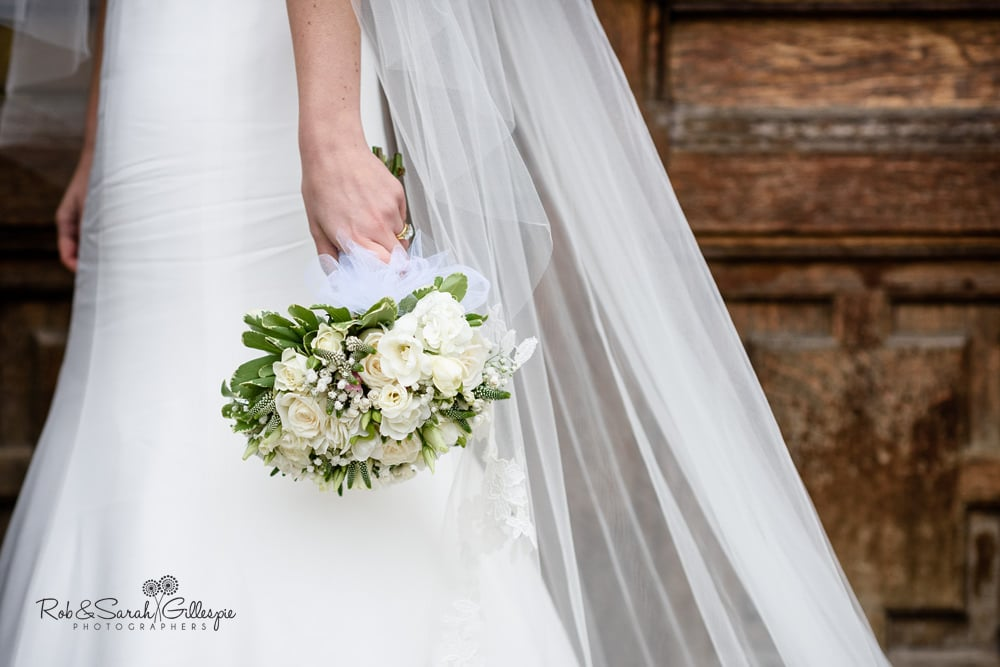 Bride holds bouquet at her side with veil behind