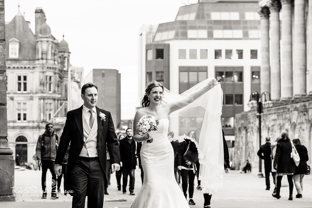 Bride and groomw walk together in Birmingham as public walk past