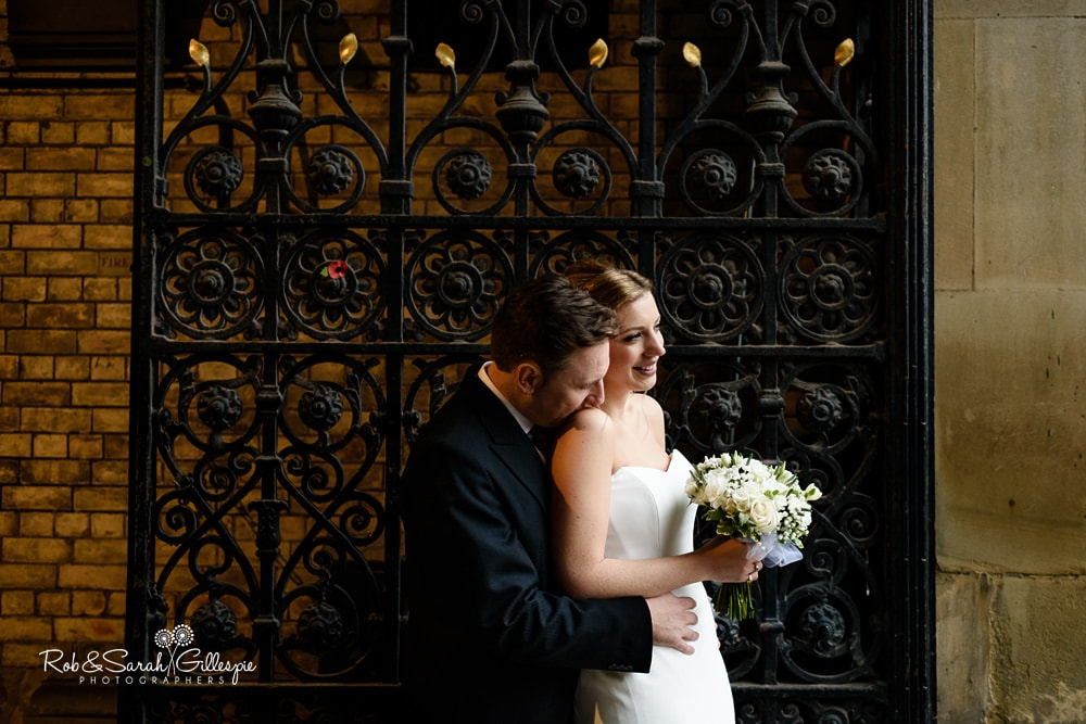 Bride and groom cuddle in front of iron gate at Birmingham Council House