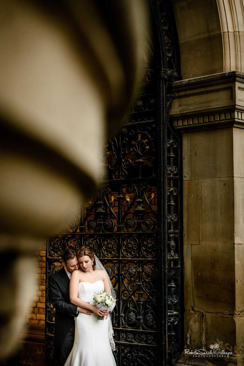 Bride and groom cuddle in front of iron gate