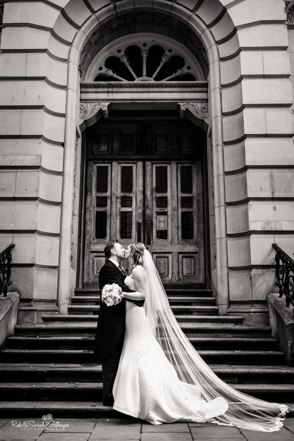 Bride and groom kiss in front of arched doorway