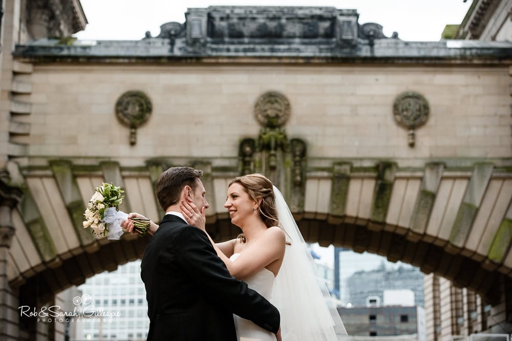 Bride and groom together underneath arched bridge of Birmingham Museum & Art Gallery