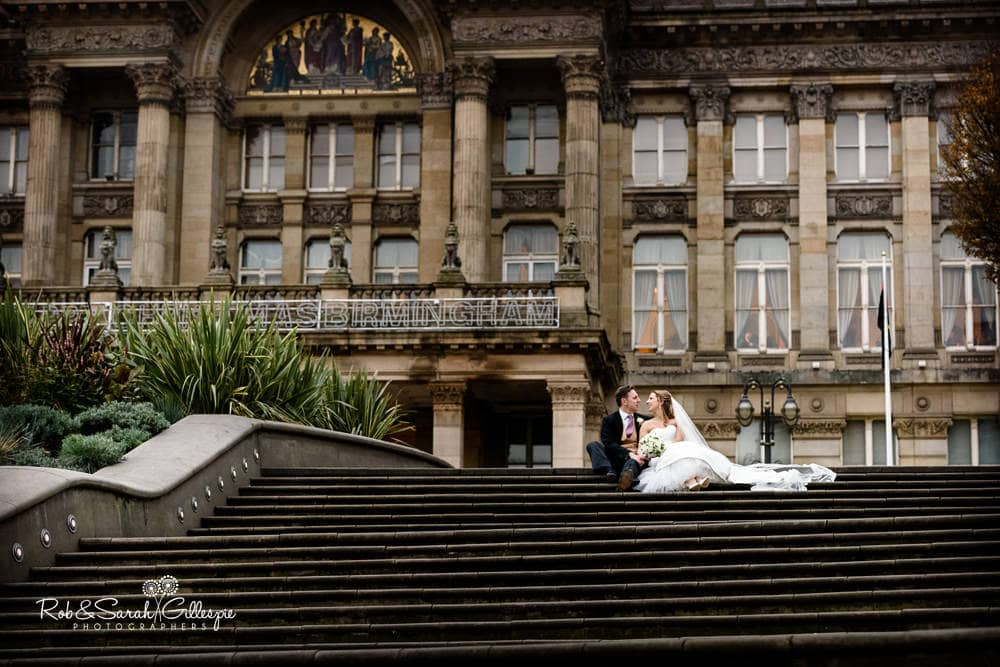 Bride and groom sit on steps in Victoria Square Birmingham, with Councl House in background