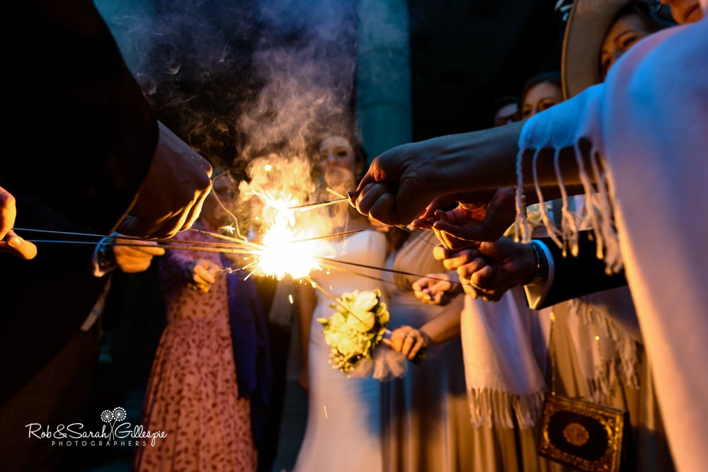 Wedding guests light sparklers