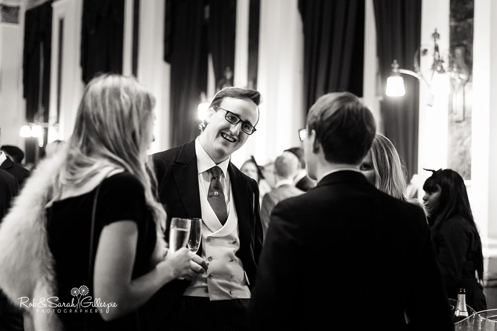 Wedding guests relax during drinks reception