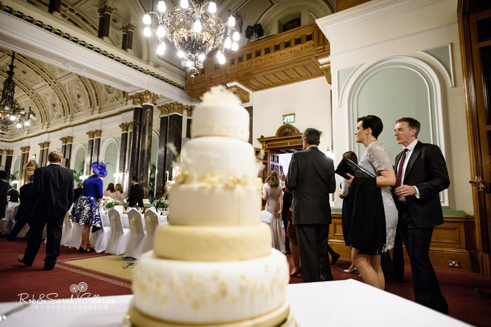 Wedding guests walk past cake as they enter Banqueting Suite for wedding reception