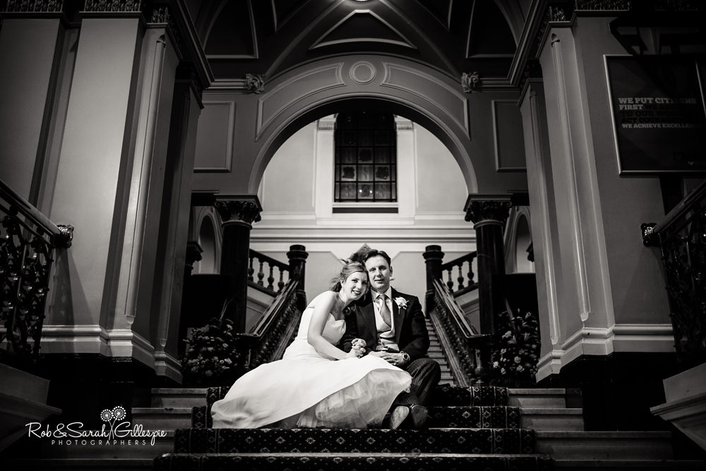 Bride and groom sitting together on staircase inside Birmingham Council House