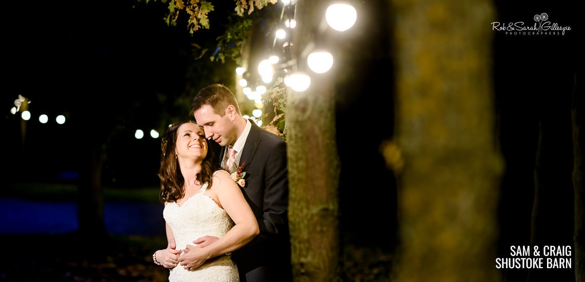 Bride and groom under light at Cripps Shustoke Barn