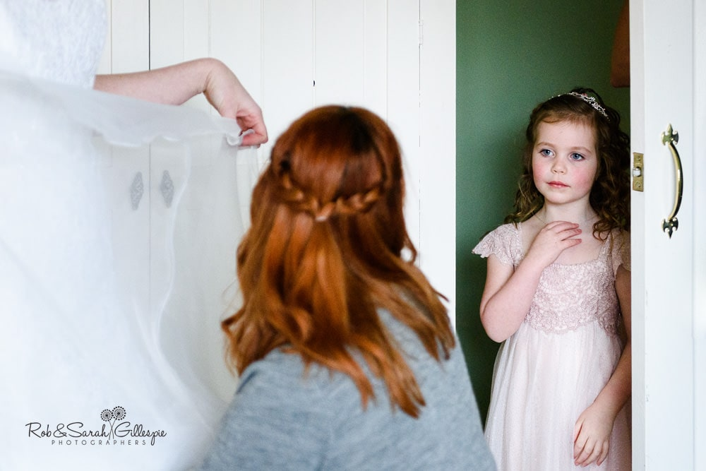 Flowergirl watches mum getting ready for wedding