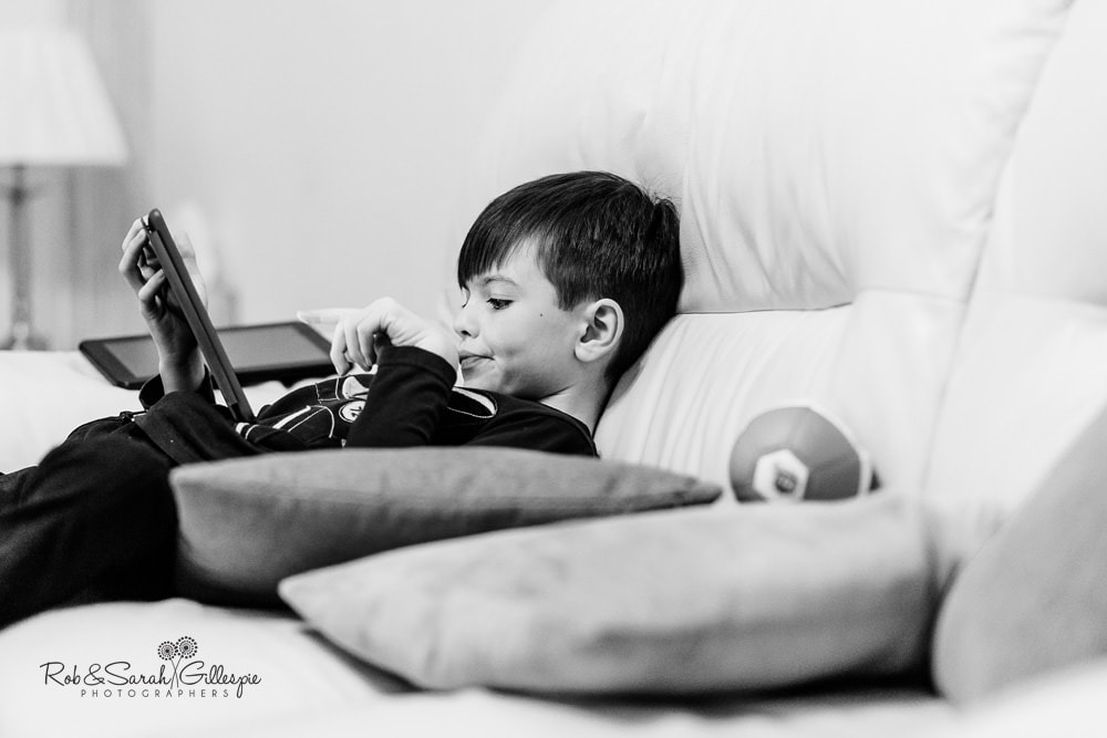 Pageboy plays with tablet before getting ready for wedding