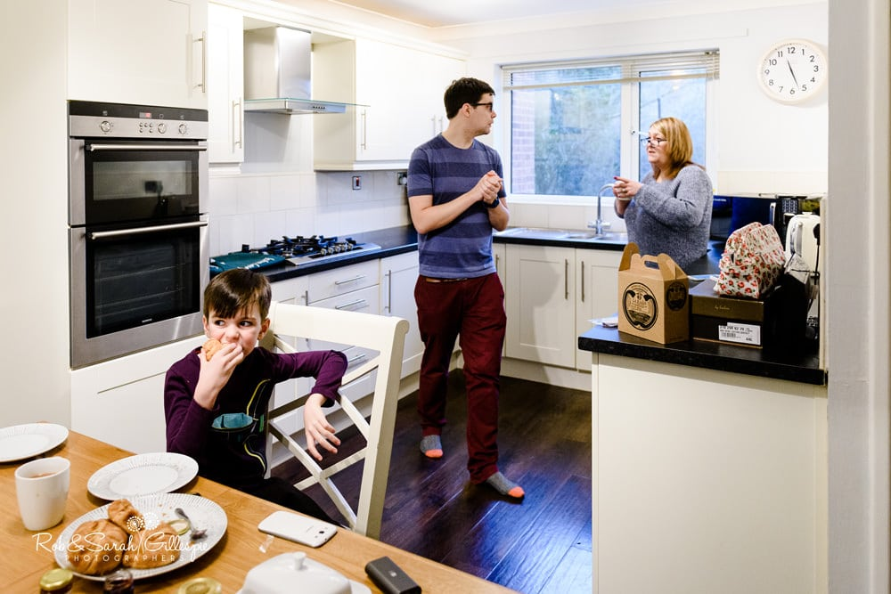 Page boy, groom and mum chat over breakfast in kitchen
