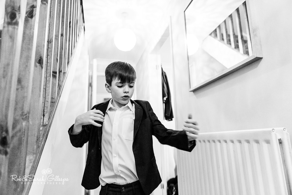 Pageboy puts on jacket while getting ready for wedding