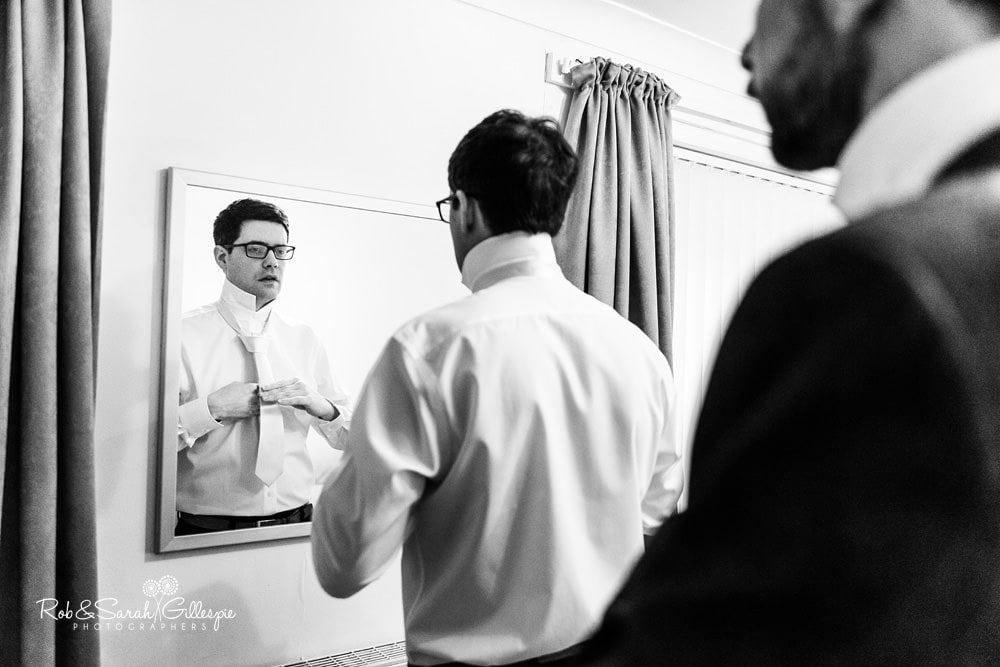 Groom and best man adjust ties in mirror