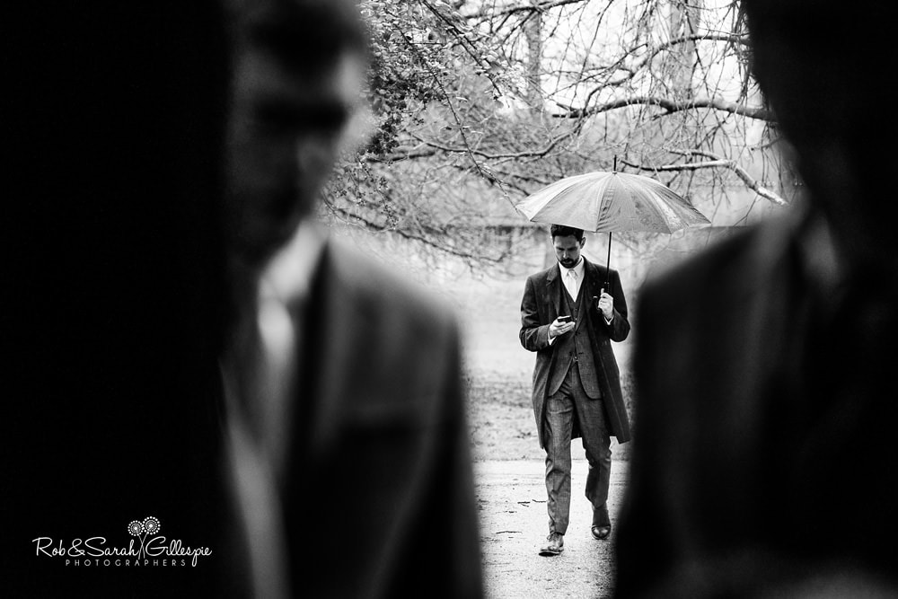 Best man arrives for wedding at Avoncroft Museum holding umbrella