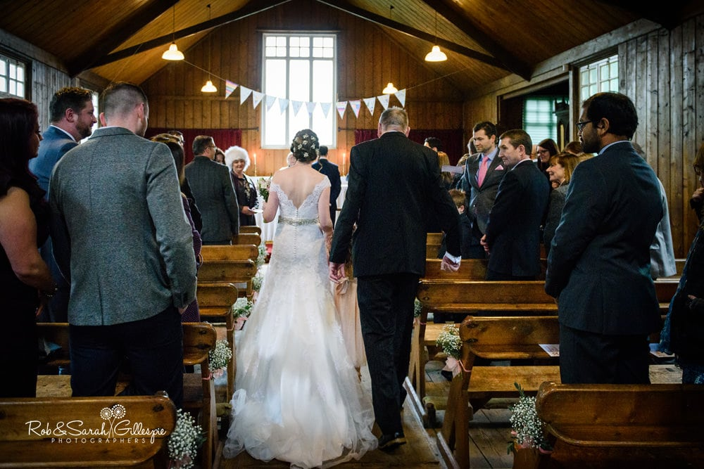 Bride and father walk up aisle in Mission Church at Avoncroft Museum